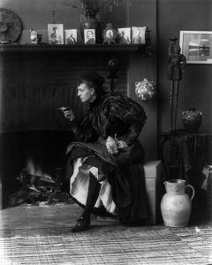 800px-Frances_Benjamin_Johnston,_full-length_portrait,_seated_in_front_of_fireplace,_1896
